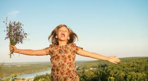 La fille heureuse saute au ciel dans le pré jaune au coucher du soleil Photographie stock libre de droits