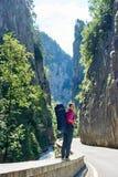 La fille heureuse se tient sur la route de montagne des montagnes de Carpathiens de Roumain photographie stock