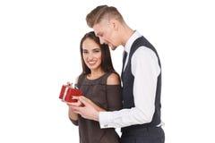 La fille heureuse tenant un boîte-cadeau et souriant, un type embrasse une fille par derrière Jour du `s de Valentine D'isolement Photos libres de droits
