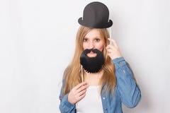 La fille heureuse tient l'accessoire de cabine de photo Images stock