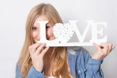 La fille heureuse tient l'amour de mot Image stock