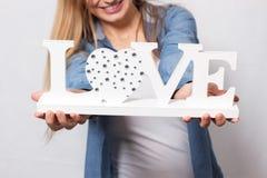 La fille heureuse tient l'amour de mot Photographie stock