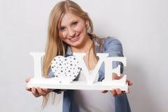 La fille heureuse tient l'amour de mot Photographie stock libre de droits