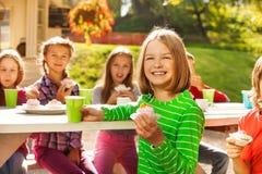 La fille heureuse tient le petit gâteau avec se reposer d'enfants Photo stock
