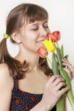 La fille inhale l'arome des tulipes Photographie stock