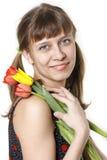 La fille inhale l'arome des tulipes Photo stock