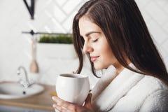 La fille inhale l'arome du café image stock