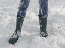 La fille jeans et à Wellington rejette la position dans la neige Photographie stock libre de droits