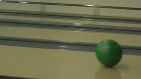 La fille jette le whick de boule de bowling roule le long de l'allée et se brise dans des quilles banque de vidéos