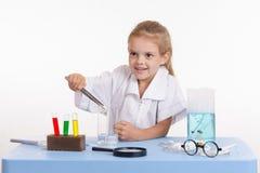 La fille jette un morceau de réactif dans le flacon dans la classe de chimie Images stock