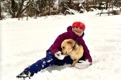 La fille joue avec le chien dans la neige et lui donne un baiser photographie stock