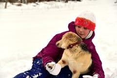 La fille joue avec le chien dans la neige et lui donne un baiser image stock