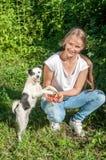 La fille joue avec un chien Photos stock