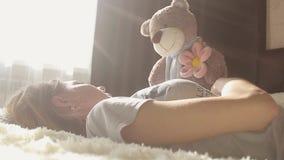 La fille joue avec un ours de nounours et sourit tout en se reposant sur son lit à la maison banque de vidéos