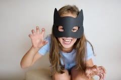 La fille joue dans un masque qui a réussi tout seul de chat noir photographie stock libre de droits