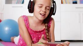 La fille joue la musique sur son smartphone chantant le long clips vidéos