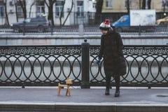 La fille joue sur la rue avec un chien imaginaire, qui est réellement une lampe images stock