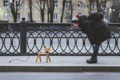 La fille joue sur la rue avec un chien imaginaire, qui est réellement une lampe Images libres de droits