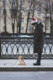 La fille joue sur la rue avec un chien imaginaire, qui est réellement une lampe Photo libre de droits