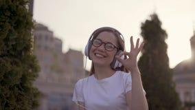La fille joyeuse dans de grands écouteurs montre le geste correct étudiant réussi 4K clips vidéos