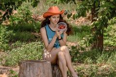 La fille juge la boîte remplie de cerises organiques contre le contexte du jardin Photo libre de droits