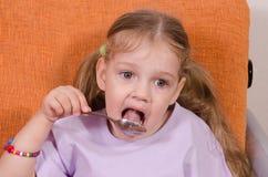 La fille lèche une cuillère avec du miel Photographie stock libre de droits