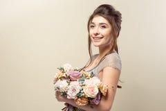 La fille ?l?gante avec une coupe de cheveux dans une robe et un maquillage bleus doux tient un bouquet d'un bouquet ?l?gant des f image libre de droits