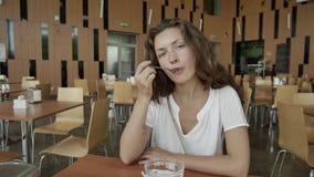 La fille a la jeune fille de petit déjeuner dans un café banque de vidéos