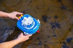 La fille lance un bateau de jouet dans la crique de for?t photographie stock libre de droits