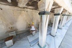 La fille lave des mains dans la mosquée de Sultanahmet Image libre de droits