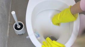 La fille lave la toilette dans les gants en caoutchouc avec une éponge banque de vidéos