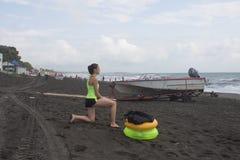 La fille, le hors-bord et le jaune, anneau de flottement vert sur la plage, croisement, nuages, ondule images stock