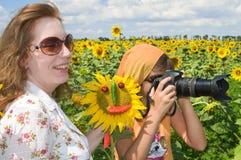 La fille le photographe et son aide. Photographie stock libre de droits