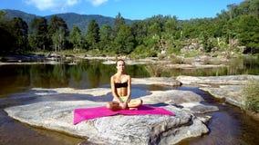 La fille a le repos faisant le yoga parmi la rivière et les montagnes éloignées banque de vidéos
