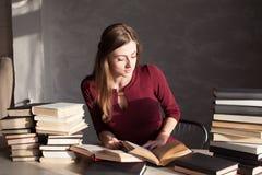 La fille lisant un livre dans la bibliothèque se prépare à l'examen Images libres de droits