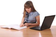 La fille lit l'ordinateur portable de configurations tacheté par livre images libres de droits