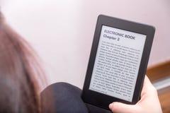 La fille lit un roman avec un lecteur d'eBook images stock