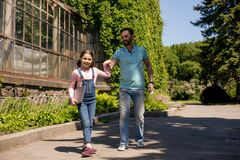 La fille mène son extérieur d'ordinateur portable de While Holding Silver de père photographie stock libre de droits