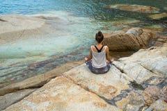 La fille méditant sur des pierres par la mer, l'emprunt de fille avec du yoga l'île Samui, yoga en Thaïlande Photographie stock libre de droits