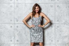 La fille magnifique de brune dans une robe égalisante grise merveilleuse pose contre le mur gris image stock