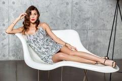 La fille magnifique de brune dans une robe égalisante grise merveilleuse s'étend dans un fauteuil blanc élégant contre le mur gri image libre de droits