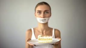 La fille maigre avec le gâteau attaché du ruban adhésif de participation de bouche, refuse de manger doux, régime de bas-CARB photo libre de droits