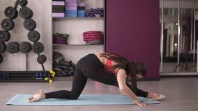 La fille maigre flexible s'étire avant que la fente, faisant la fente, s'étirant à la jambe gauche et rend une pente en avant des banque de vidéos
