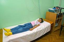 La fille malade adopte la procédure dans un bureau physiothérapique photographie stock libre de droits