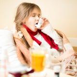 La fille malade avec la maladie respiratoire se situant dans le lit et employant inhalent Photos libres de droits