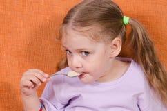 La fille mange la cuillère de miel Photographie stock libre de droits