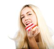 La fille mange le coeur rayé coloré Photographie stock