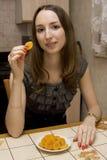 La fille mange les abricots secs Photo stock