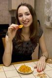 La fille mange les abricots secs Photos stock