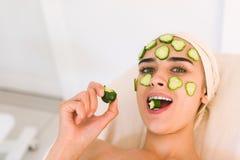 La fille mange un concombre Photographie stock libre de droits